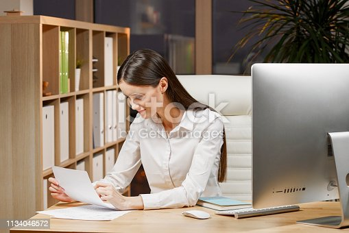 840623374 istock photo Cute young lady is concentrated on ideas for new start up. She is in casual shirt, sitting at her workplace and studying documents 1134046572