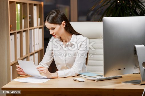 840623374 istock photo Cute young lady is concentrated on ideas for new start up. She is in casual shirt, sitting at her workplace and studying documents 1134046585
