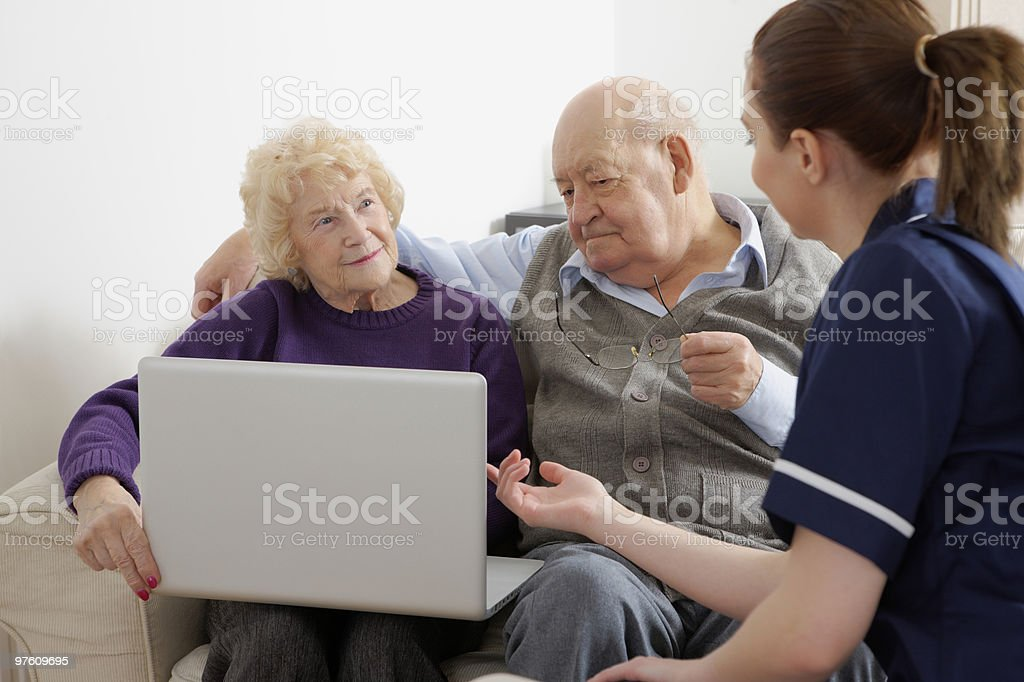 Cute young lady showing something on laptop to senior couple royalty-free stock photo