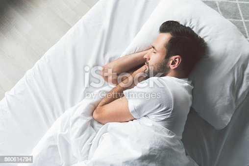 istock Cute young man sleeping on bed 860614794