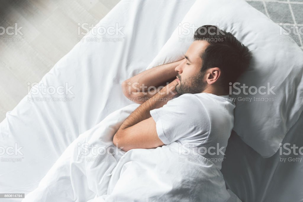 Cute young man sleeping on bed stock photo