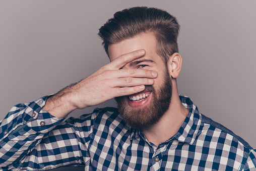 636829368 istock photo cute  young man with beard hiding his face with palms 636830476