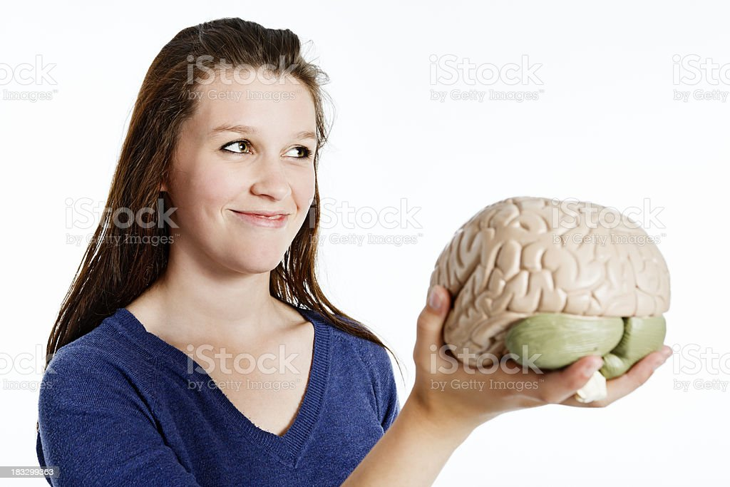 Cute young redhead holds model brain and smiles royalty-free stock photo