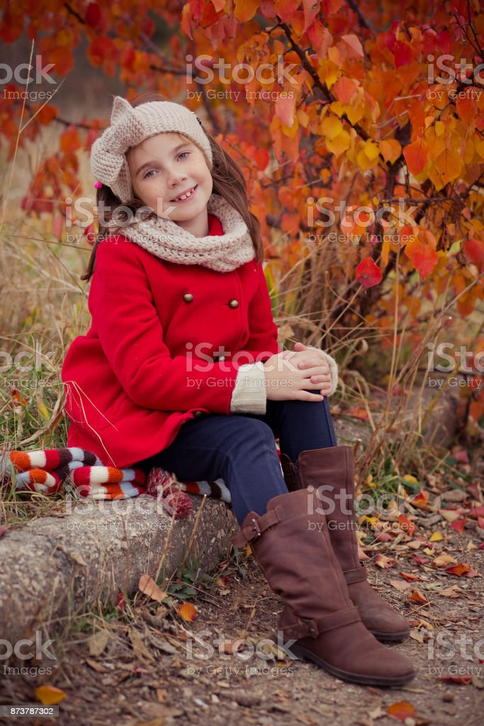 Cute young russian girl stylish dressed in warm red handmade jacket blue jeans boots and hooked headband scarf posing in autumn colorful forest pathway Face with freckling stock photo