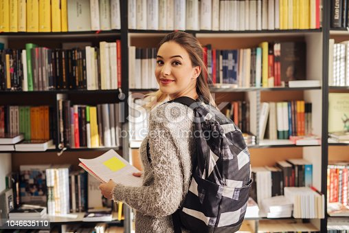istock Cute young school girl with backpack on her back standing in library in front of the bookshelf and looking at camera. 1046635110