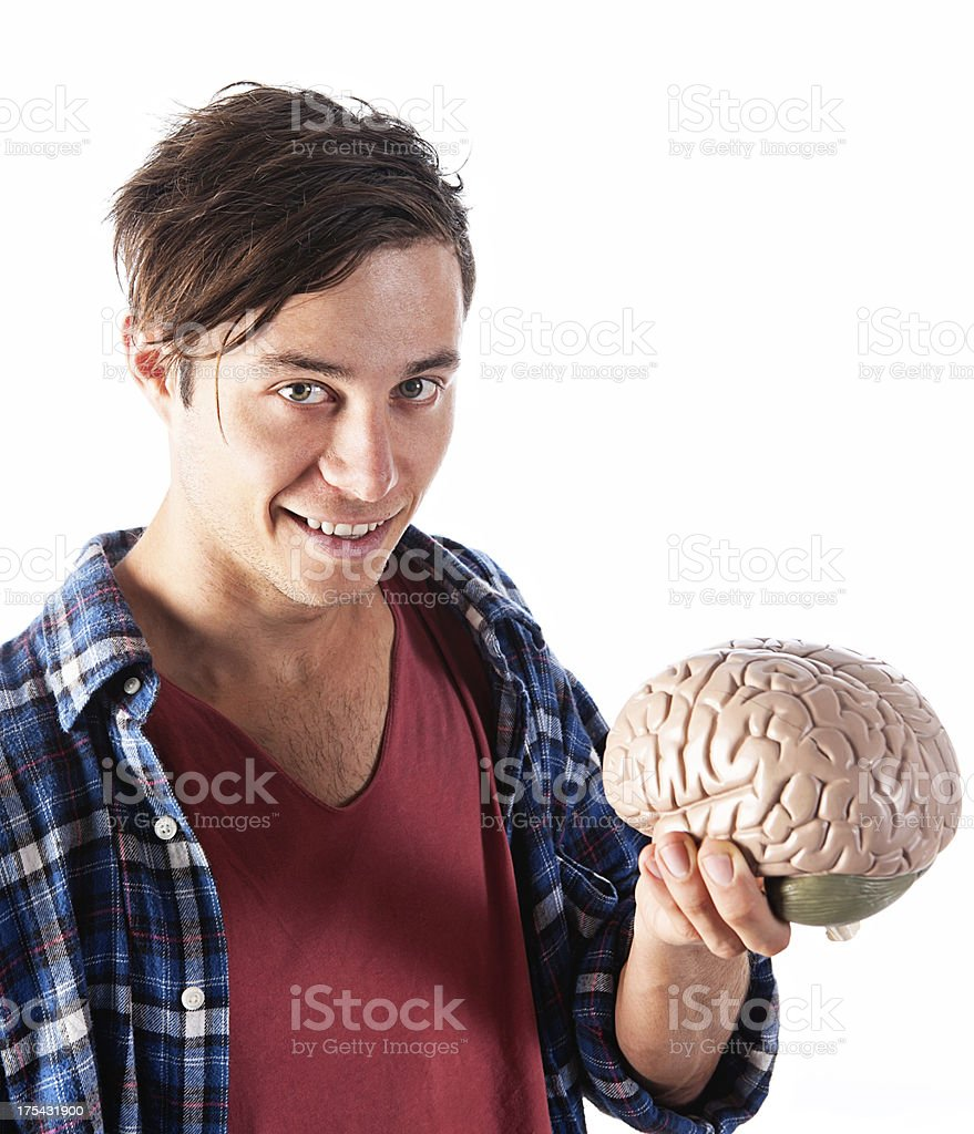 Cute young smiling geek holds out model brain royalty-free stock photo