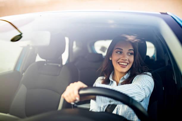ładny młody sukces szczęśliwa brunetka kobieta prowadzi samochód. - car zdjęcia i obrazy z banku zdjęć
