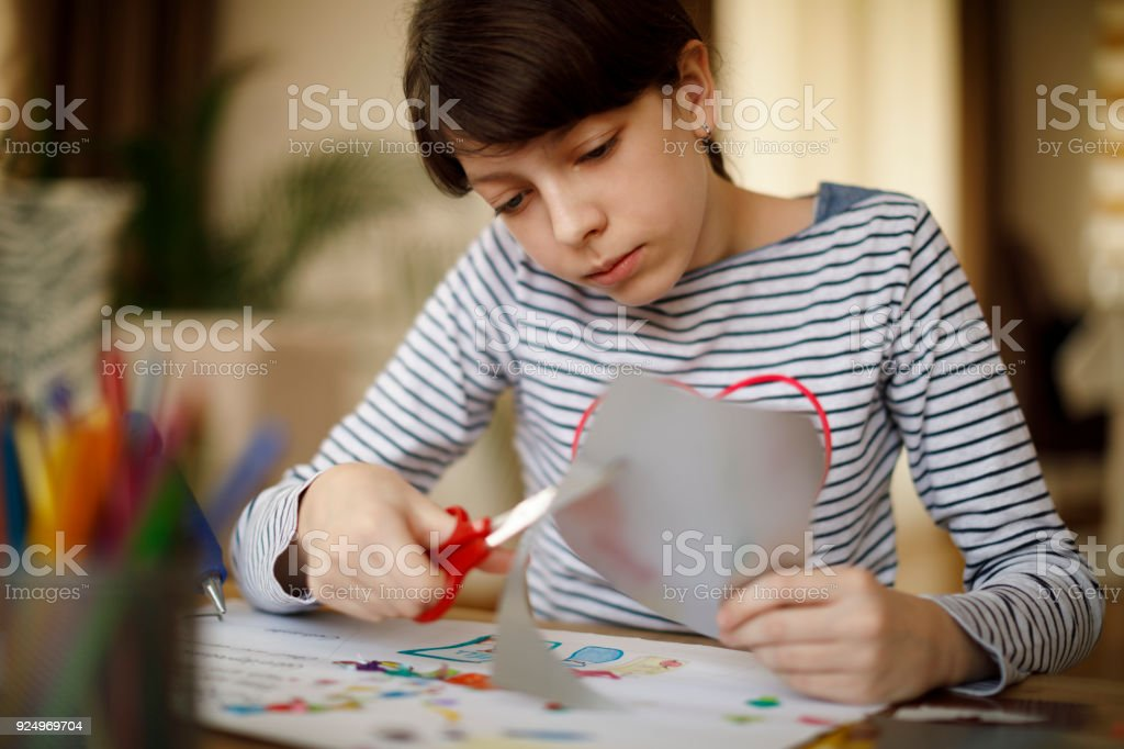 Cute young teenage girl doing homework project - Stock image .