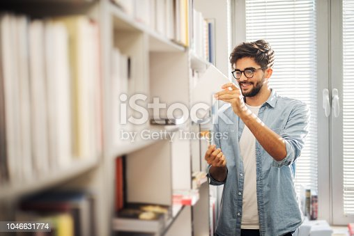 istock Cute young urban male student standing in bright library and taking book from bookshelf. Standing alone and smiling. 1046631774