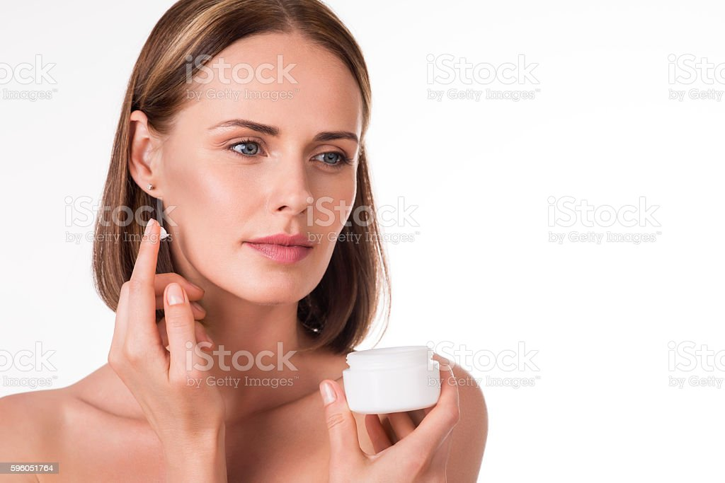 Cute young woman applying cosmetics royalty-free stock photo
