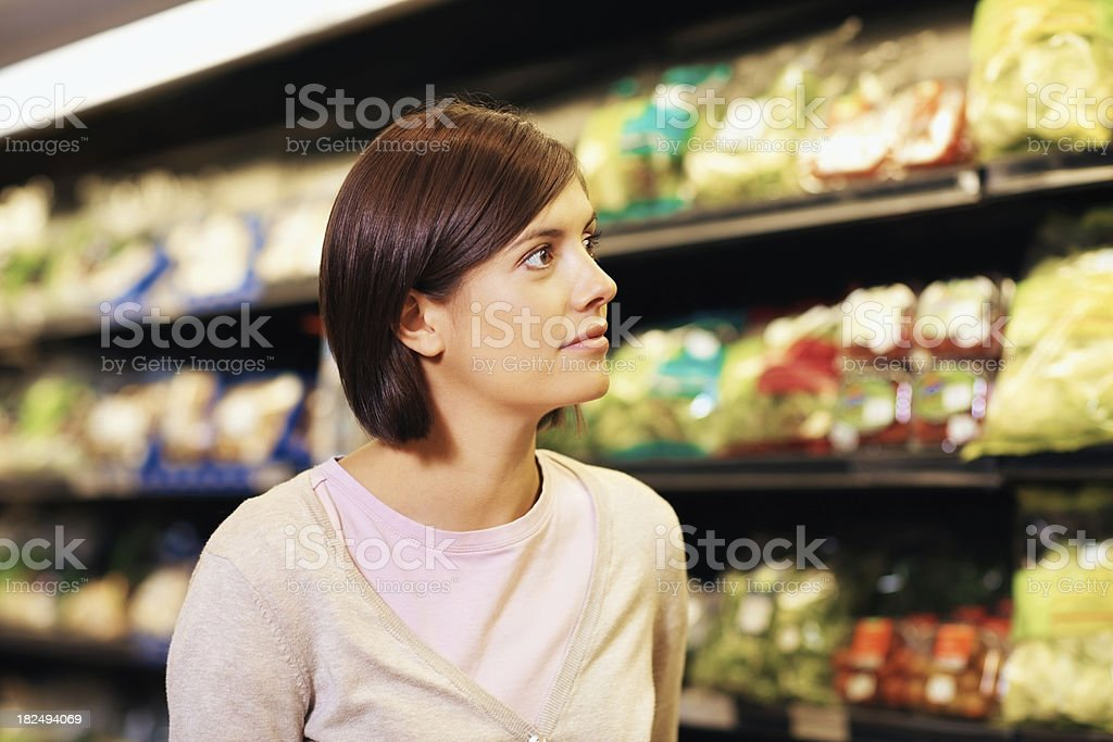 Cute young woman at a super market shopping for groceries royalty-free stock photo