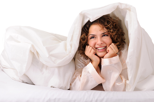 Cute young woman day dreaming under blanket in bed - XXXL image