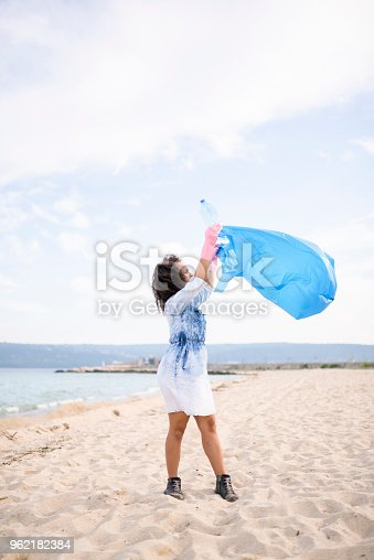 962184460 istock photo Cute young woman during local clean up at the beach 962182384