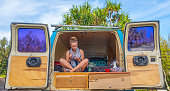 Cute Young Woman Eating Breakfast On Vacation In The Back Of Rental Van