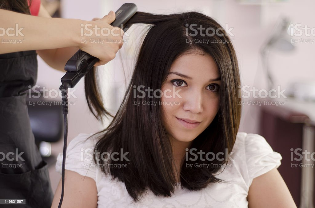 Cute young woman getting her hair done royalty-free stock photo