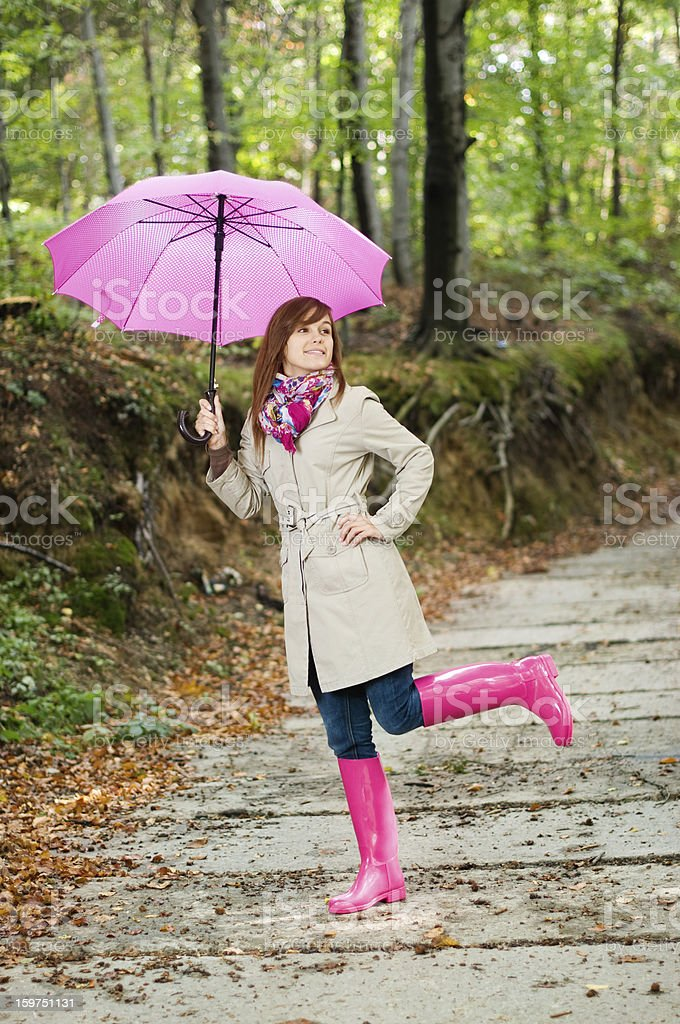 Cute young woman having fun after raining royalty-free stock photo