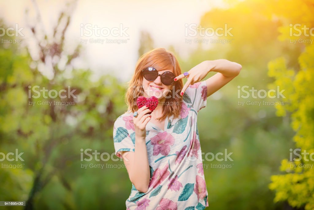 Cute young woman holding a heart - shaped sign and two fingers - symbols for peace. stock photo