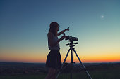 Cute young woman holding astronomical telescope and looking at the sky.