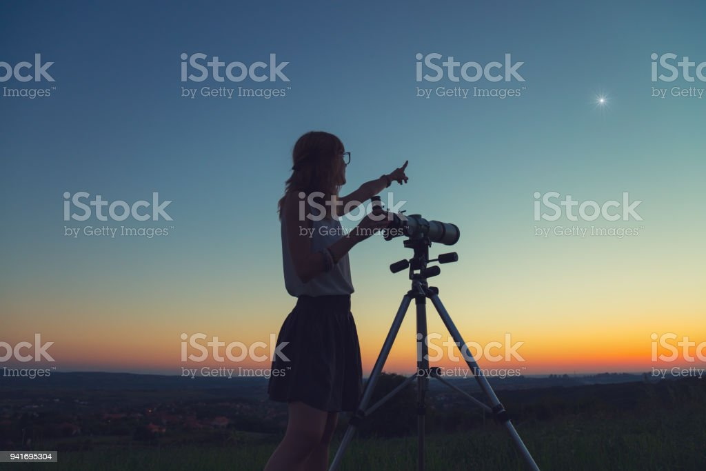 Cute young woman holding astronomical telescope and looking at the sky. stock photo