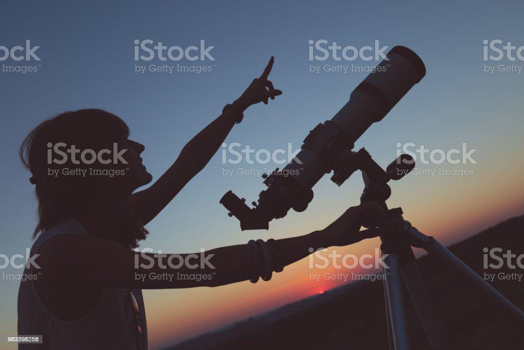 Urocza młoda kobieta trzymająca astronomiczny teleskop i patrząca w niebo. - Zbiór zdjęć royalty-free (Analizować)