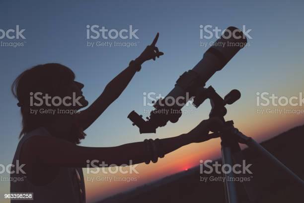 Urocza Młoda Kobieta Trzymająca Astronomiczny Teleskop I Patrząca W Niebo - zdjęcia stockowe i więcej obrazów Analizować