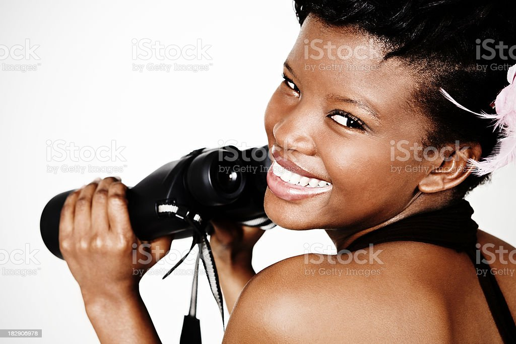 Cute young woman holding binoculars smiles over her shoulder royalty-free stock photo