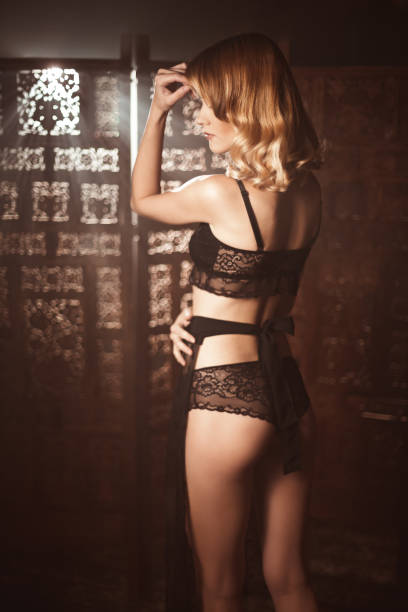 Cute young woman in a old-fashion lace lingerue posing against carved screen stock photo