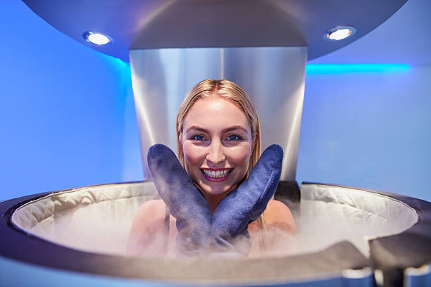 Cute young woman in cryosauna booth Portrait of a cute young woman in cryosauna booth for full body cryotherapy. Caucasian female in freezing chamber with nitrogen vapors. cryotherapy stock pictures, royalty-free photos & images