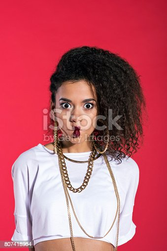 807419930istockphoto Cute young woman in hip-hop style against red background 807418954