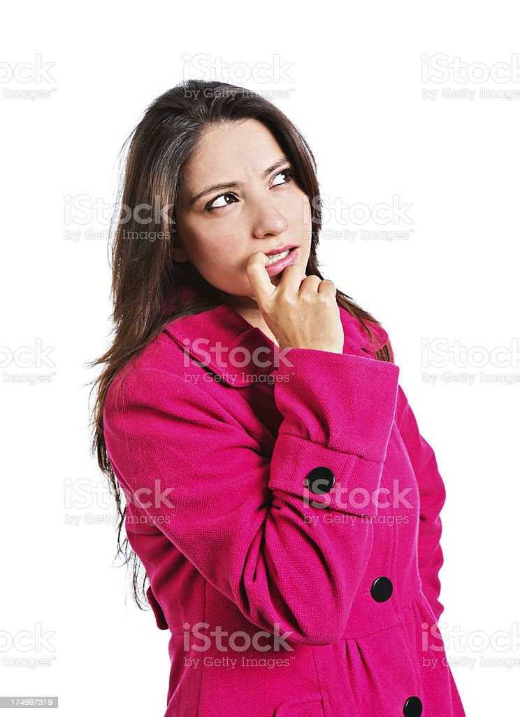 Cute young woman in pink looks worried, finger to mouth royalty-free stock photo