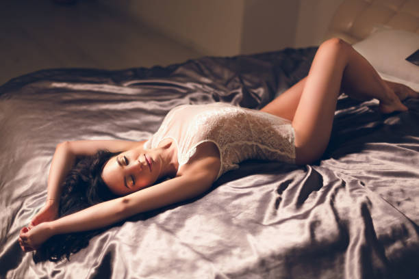 Cute young woman in white lace bodysuit lying posing in big hotel bed stock photo
