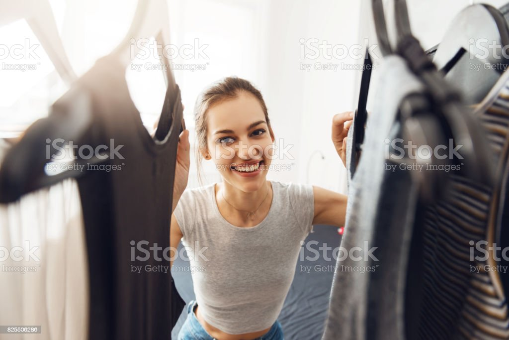 Cute, young woman looking for something to wear stock photo