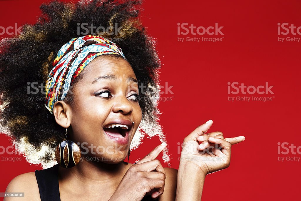 Cute young woman looks sideways, pointing at blank space royalty-free stock photo