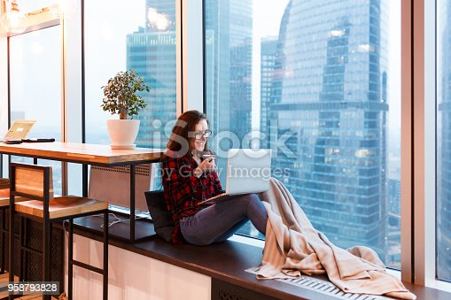1162297213 istock photo Cute young woman outsourcing designer working in creative studio sitting under blanket with mug of coffee and working at the computer on background of large window overlooking the skyscrapers 958793828