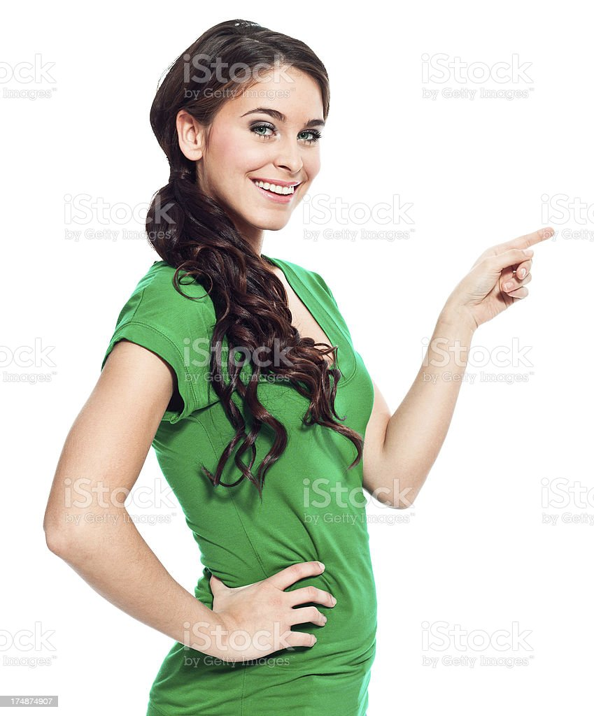 Cute young woman pointing Portrait of beautiful young woman pointing at the copy space and smiling at the camera. 20-24 Years Stock Photo