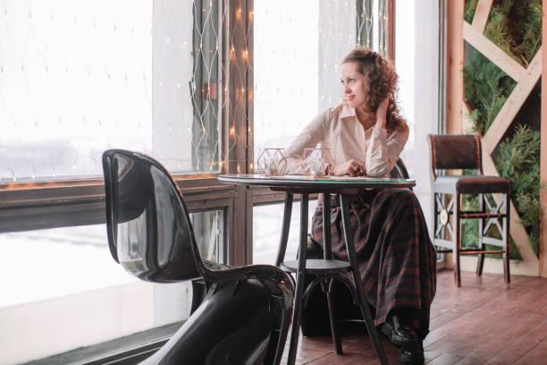 nette junge Frau sitzt an einem Tisch in einem Café – Foto