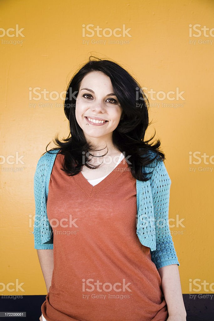 cute young woman standing infront of bright yellow wall royalty-free stock photo