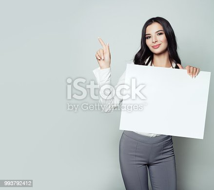 Cute young woman student with white blank paper banner background with copy space pointing her finger. Business, startup or education concept
