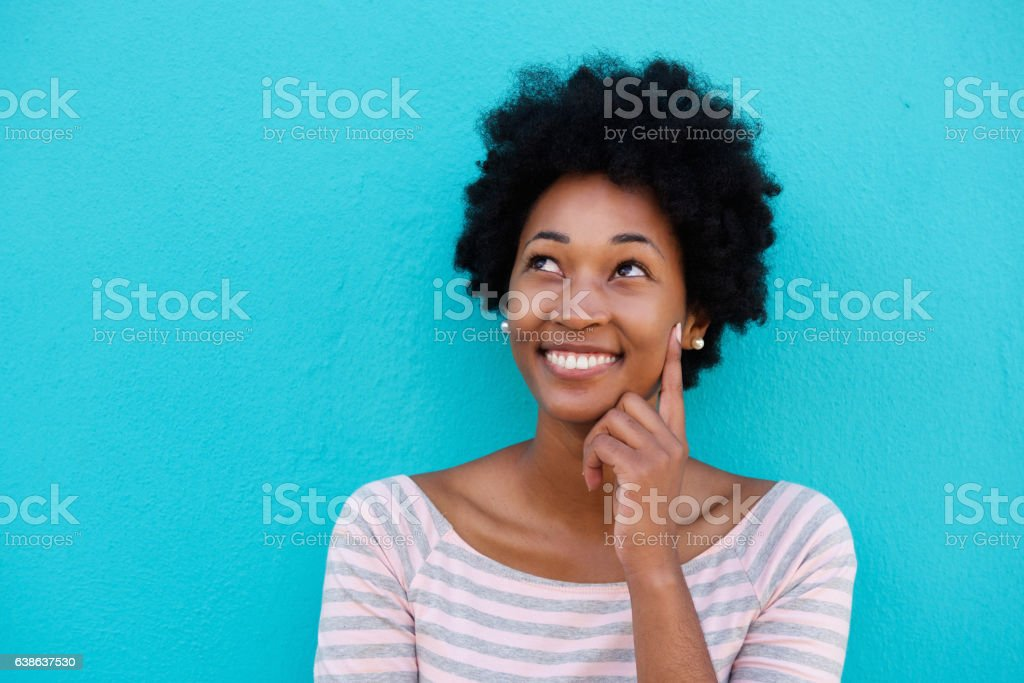 Cute young woman thinking and looking up stock photo