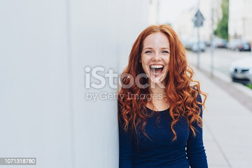 Cute young woman with a lovely sense of humour standing leaning against a white exterior wall with copy space in an urban street laughing at the camera