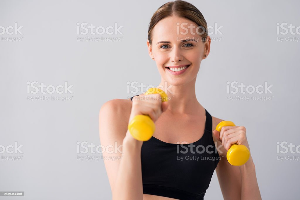 Cute young woman with dumb bells royalty-free stock photo