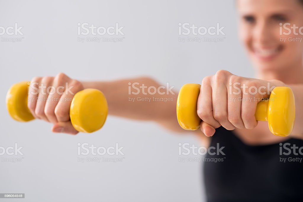 Cute young woman with dumbbells royalty-free stock photo