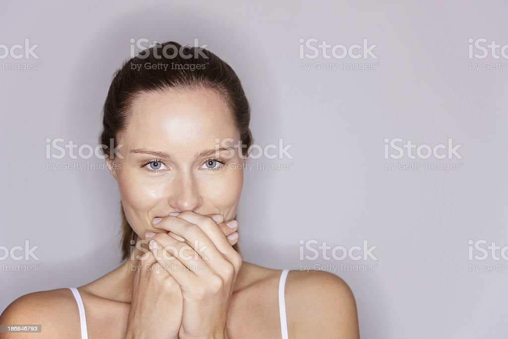 Cute young woman with hands over mouth royalty-free stock photo