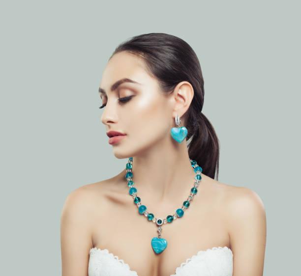 nette junge frau mit make-up, silber halskette und ohrringe mit diamanten und blauen steinen - türkise haare stock-fotos und bilder