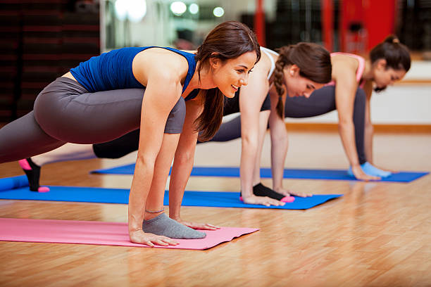 Cute young women doing yoga Beautiful young Hispanic women working out and enjoying their yoga class in a gym yoga class stock pictures, royalty-free photos & images