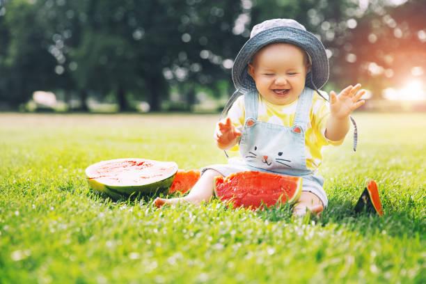 Más lindo sonriente niña comiendo sandía sobre hierba verde durante el verano. - foto de stock