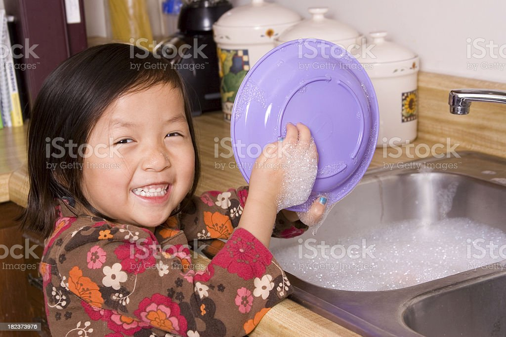 Cutie washing dishes stock photo