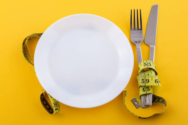 Cutlery and a white plate with measuring tape on a yellow background, the concept of weight loss and diet stock photo