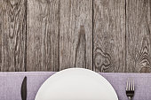 Cutlery and empty white plate on a wooden table with copy space. Food background