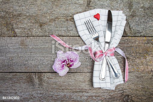 Cutlery decorated hearts, orchid flower and red ribbon for Valentine's Day or wedding